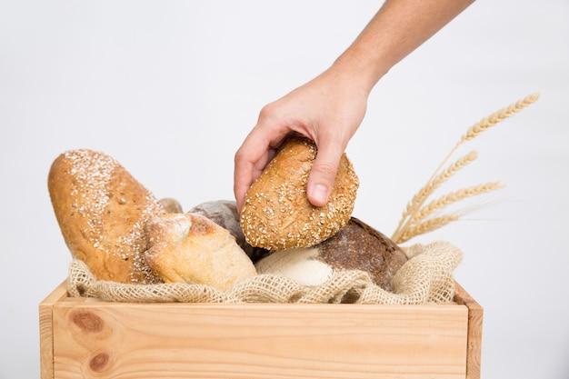 Close-up van menselijke hand die brood plaatst in rustieke houten doos