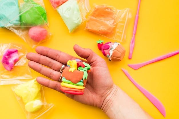 Close-up van menselijke hand die decoratieve klei op gele achtergrond toont