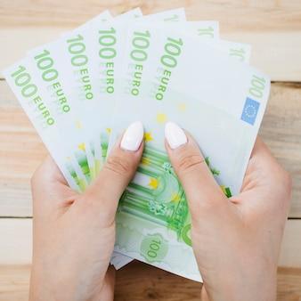 Close-up van menselijke hand die honderd euro bankbiljetten op houten lijst houdt