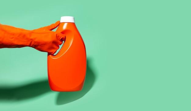 Close-up van menselijke hand die schoonmakende handschoen draagt, die wasmiddelfles van plastic op achtergrond aqua menthe kleur met exemplaarruimte en schaduwen houdt.