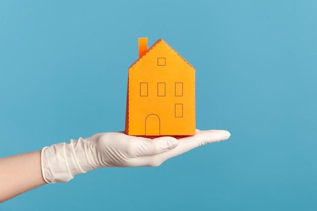 Close-up van menselijke hand in witte chirurgische handschoenen die de buitenkant van het oranje papieren huis in de hand houden.
