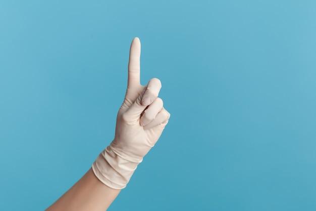Close-up van menselijke hand in witte chirurgische handschoenen die nummer één met vinger tonen of kant tonen.