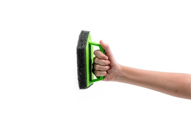 Close-up van menselijke hand met een groene plastic scrubber geïsoleerd op een witte achtergrond.