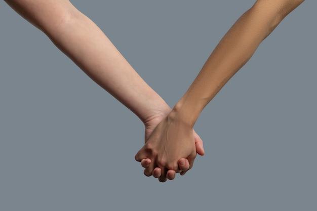 Close-up van mensen met een lichte en donkere huid die elkaars hand vasthouden