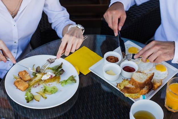 Close-up van mensen uit het bedrijfsleven handen, mannelijke en vrouwelijke ontbijten in openlucht café. maaltijden met salade, omelet, spek.