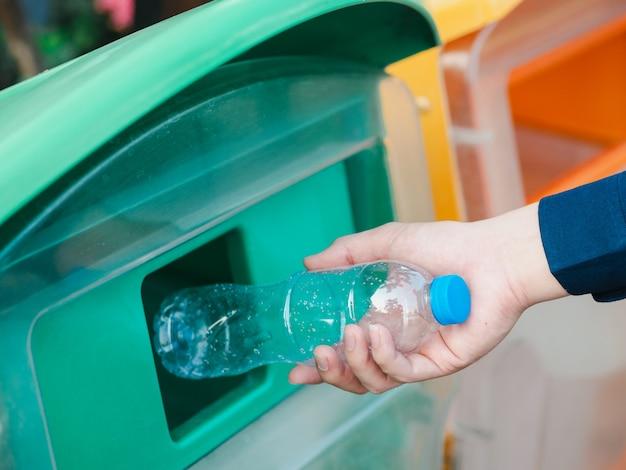 Close-up van mensenhand die lege plastic waterfles in recyclingsbak werpen.