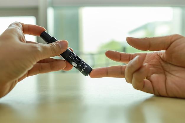 Close-up van mensenhanden die lancet op vinger gebruiken om bloedsuikerspiegel door glucosemeter te controleren