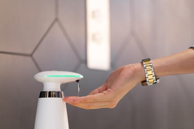 Close-up van mensenhanden met gebruik van automatische alcoholgel-dispenser met washand om coronavirus (covid-19) pathogenen te desinfecteren en te desinfecteren.