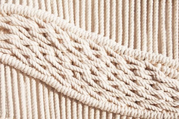Close-up van met de hand gemaakt macramé structuurpatroon. eco-vriendelijk modern breiwerk diy natuurlijk decoratieconcept in het interieur. handgemaakte macramé 100% katoen. vrouwelijke hobby.