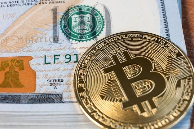 Close up van metalen glanzende bitcoin crypto valuta munt op amerikaanse dollarbiljetten. elektronisch gedecentraliseerd geldconcept.