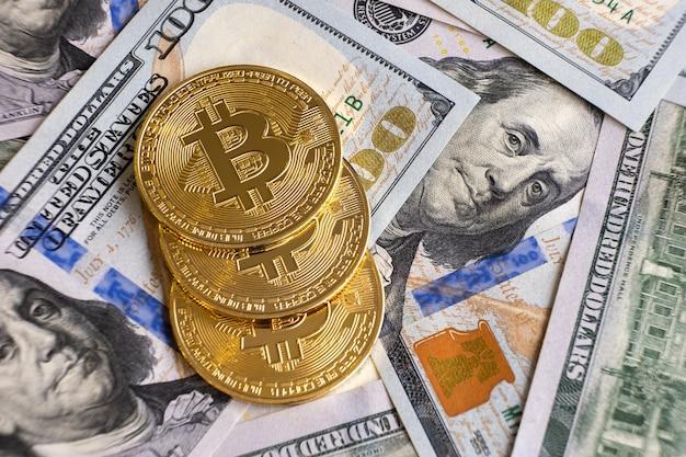 Close up van metalen glanzende bitcoin crypto valuta munten op amerikaanse dollarbiljetten. elektronisch gedecentraliseerd geldconcept.
