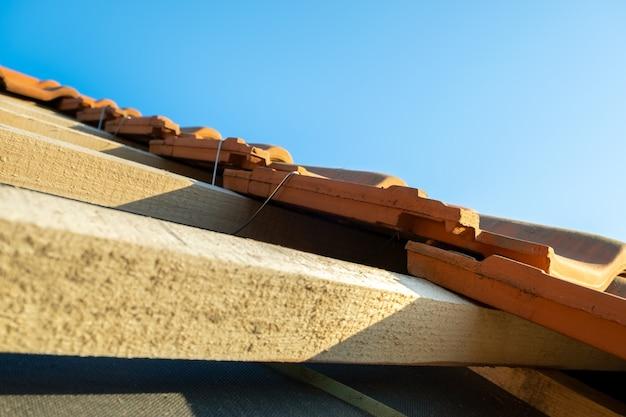 Close-up van metalen montageanker voor installatie van gele keramische dakpannen gemonteerd op houten planken die het dak van een woongebouw in aanbouw bedekken.