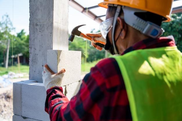 Close-up van metselaarbouwer gebruikt een hamer om te helpen met geautoclaveerde cellenbetonblokken. muren, stenen plaatsen op de bouwplaats
