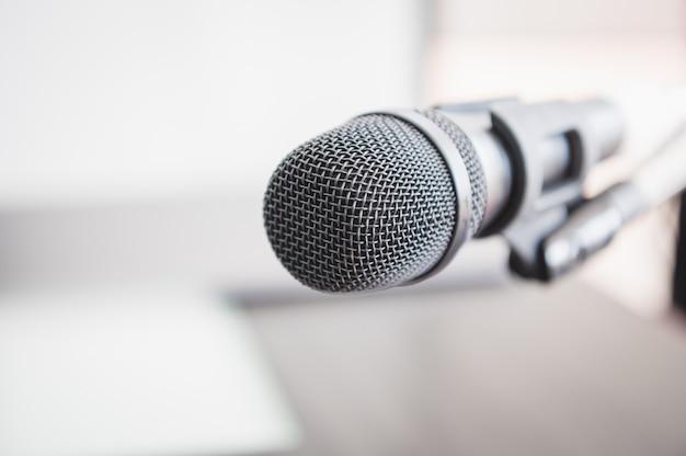 Close-up van microfoon in collegezaal achtergrondtoespraak in de zaal van de seminarieovereenkomstzaal. mic spreker van leraar op podium in hogeschool of universiteit. workshop evenement en entertainment uitzending concept.