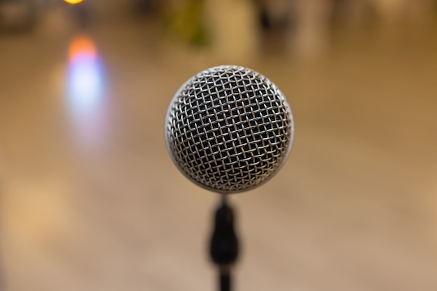 Close-up van microfoon over abstract wazig van deelnemer in seminarruimte of conferentiezaal