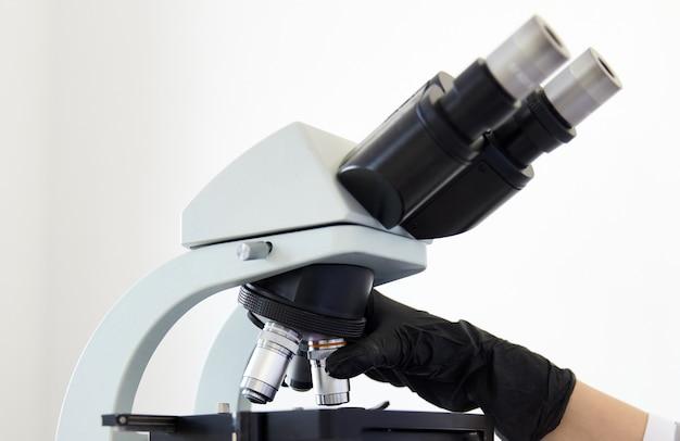 Close-up van microscoop en handen dragen van rubberen handschoenen in modern laboratorium.