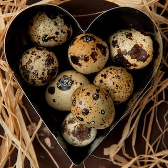 Close-up van mini-eieren in hartvormige doos op stro achtergrond