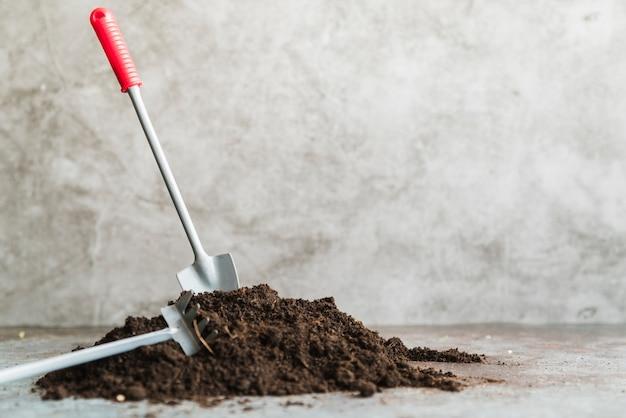Close-up van mini tuinierende troffel en vork tegen concrete achtergrond