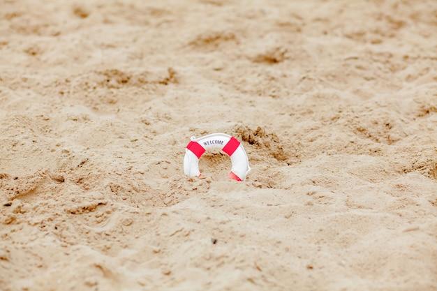 Close-up van miniatuur reddingsboei graven in het zand op het strand.
