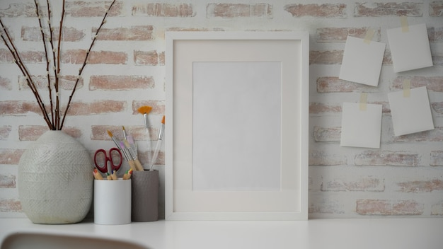 Close-up van minimale werkruimte van de kunstenaar met leeg frame, tekengereedschappen, keramische vaas en kopie ruimte