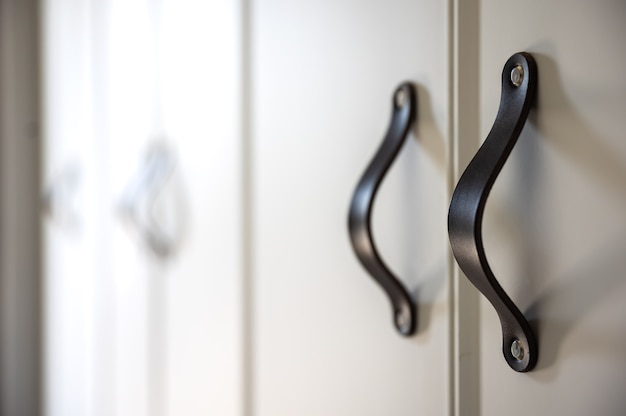 Close up van minimalistische witte meubels met zwarte handgrepen, keukenkast, details.
