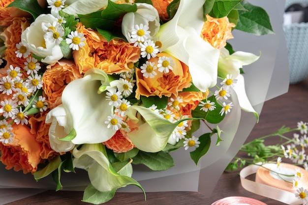 Close up van mode moderne boeket van verschillende bloemen op houten oppervlak. masterclass. cadeau voor bruid op bruiloft, moederdag, vrouwendag. romantische lentemode. heldere kleuren van gevoelens.