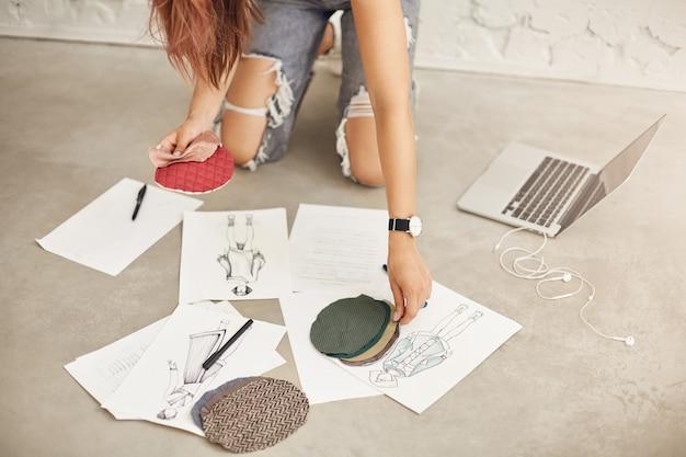 Close-up van modeontwerpster in het midden van haar werk met behulp van laptop en tekeningen en illustraties van haar nieuwe collectie