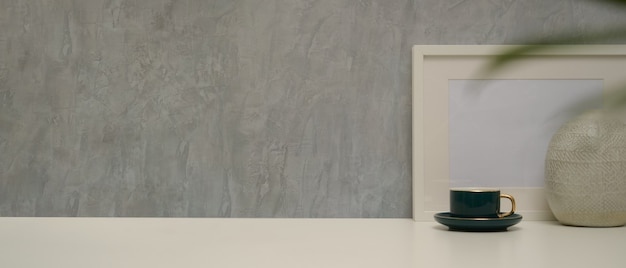 Close-up van modern interieur met kopie ruimte, mock-up frame, vaas en kopje op bureau met zoldermuur