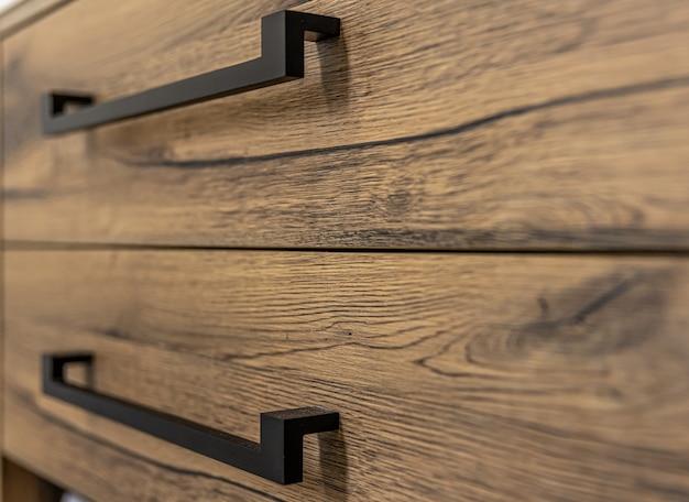 Close-up van moderne donkere houten meubelen met zwarte handgrepen.