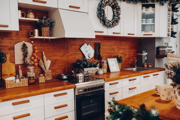 Close-up van moderne gezellige keuken in witte en bruine kleuren met spullen, fornuis en decoratieve dennenboomtakken. kerst versiering.