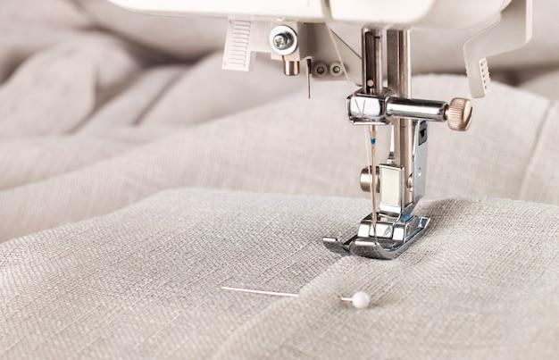Close-up van moderne naaimachine naaivoet en naald naaien kledingstuk.
