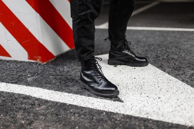 Close-up van modieuze leren seizoenslaarzen op herenbenen. jonge kerel in vintage jeans in trendy schoenen staat op het asfalt in de buurt van een pilaar met rood-witte lijnen. stijlvolle casual jeugdschoenen voor heren.
