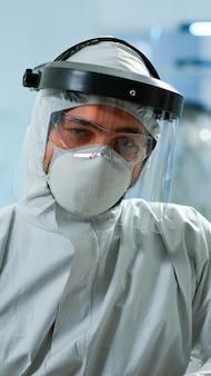 Close up van moe scheikundige arts in overall kijken camera werken in wetenschappelijk laboratorium. wetenschapper die werkt met verschillende bacteriën, weefsel- en bloedmonsters, farmaceutisch onderzoek voor antibiotica