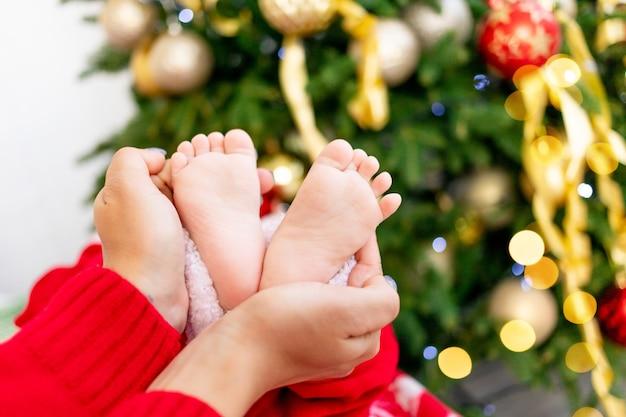 Close-up van moeder die de voeten van de baby vasthoudt bij de kerstboom met een rood hartvormig decor, het concept van nieuwjaar en kerstmis