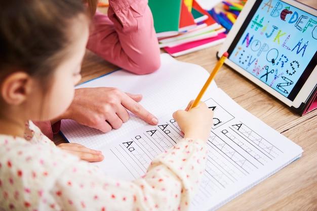 Close up van moeder die haar kind helpt met huiswerk