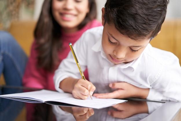 Close-up van moeder die haar zoon helpt om huiswerk te maken voor schoolspbi-kind dat notities schrijft in notitieboekjemo...