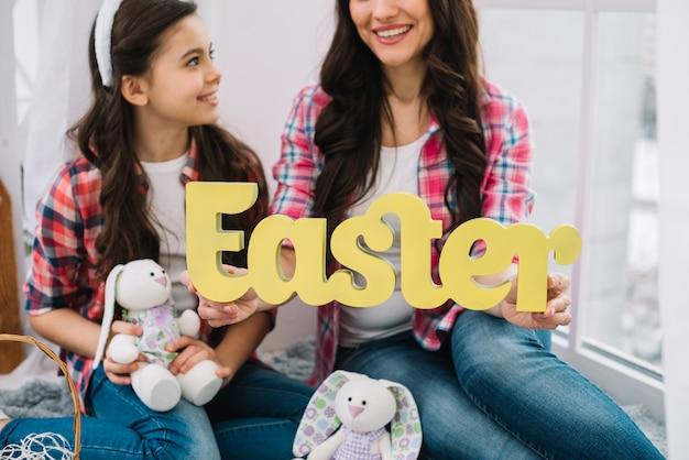 Close-up van moeder en dochter bedrijf konijn en pasen woord in de hand
