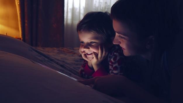 Close-up van moeder en haar kleine dochter het letten op tablet thuis.