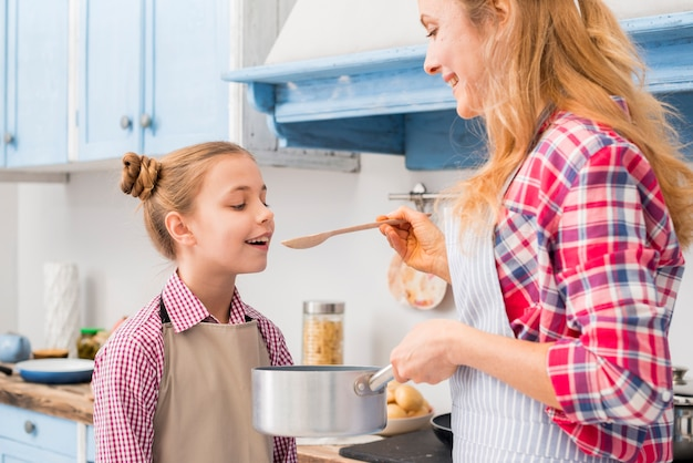 Close-up van moeder proevende soep aan haar dochter van de pan