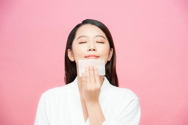 Close-up van mooi gelukkig aziatisch meisjesmodel met natuurlijke make-up die olieabsorberende bladen gebruikt, schoonheidsproduct bij studio