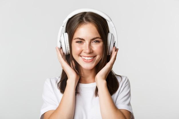 Close-up van mooi gelukkig meisje glimlachen, genieten van het luisteren naar muziek in draadloze hoofdtelefoons.