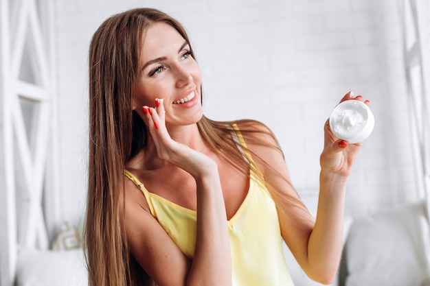 Close-up van mooi jong vrouwelijk model met verse de roomfles van de huidholding ter beschikking.