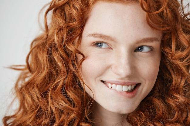 Close up van mooi meisje met krullend rood haar en sproeten glimlachend bijten lip.