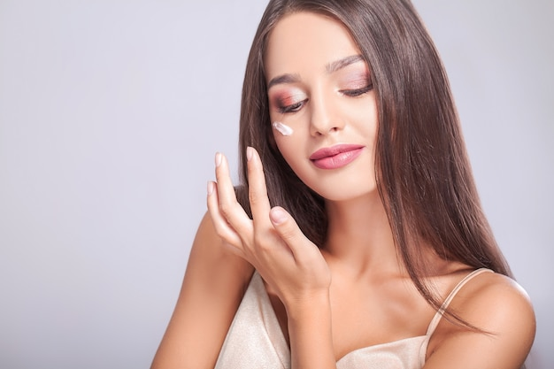 Close-up van mooi sexy glimlachend meisje die room op verse zachte zuivere huid zetten.