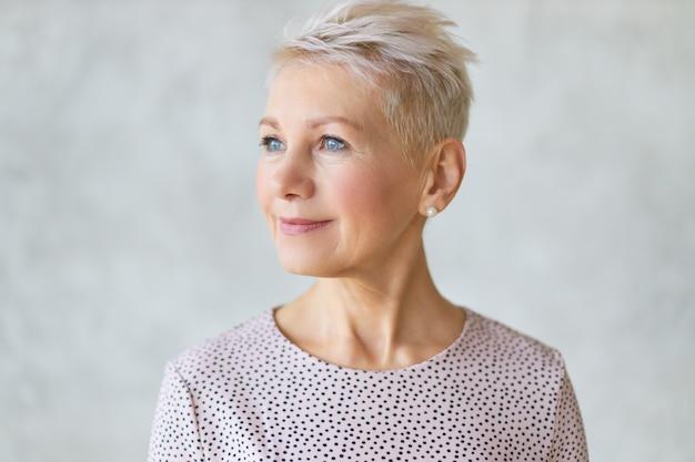 Close-up van mooie aantrekkelijke europese dame van middelbare leeftijd met stijlvol kapsel en nette make-up wegkijken met zelfverzekerde glimlach poseren geïsoleerd tegen een marmeren muur