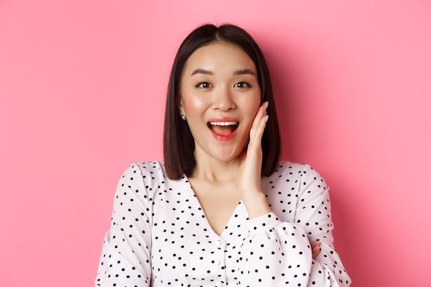 Close-up van mooie aziatische vrouw die u roept, aankondiging doet of schreeuwt, die zich over roze bevindt