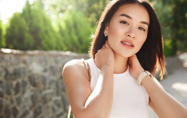 Close-up van mooie aziatische vrouw die zich in park bevindt en camera met nadenkend gezicht bekijkt