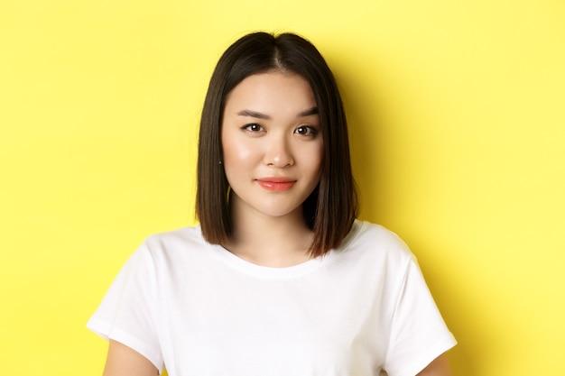 Close-up van mooie aziatische vrouw met casual make-up, wenkbrauw optrekkend en geïntrigeerd naar de camera kijkend, nieuwsgierig over gele achtergrond