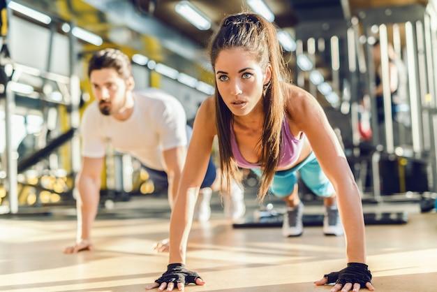 Close-up van mooie blanke vrouw doet push-ups in de sportschool.