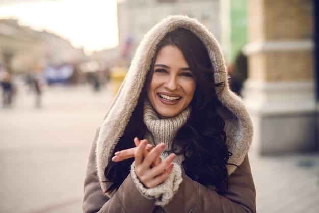 Close up van mooie blanke vrouw met lang bruin haar staande op straat bij koud weer en verwarmende handen.